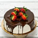Tort śmietankowo-truskawkowy z polewą czekoladową i ozdobą ze świeżych truskawek