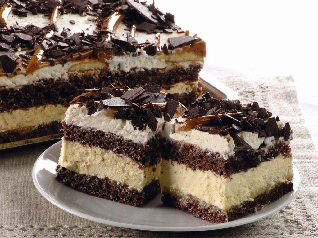 Ciasto budyniowo-kremowe, zdobione bitą śmietaną, czekoladą i karmelem